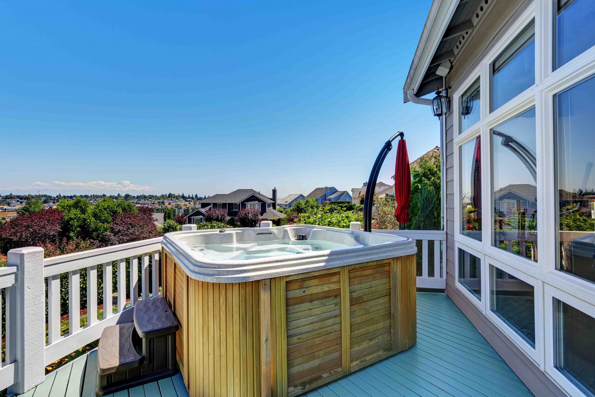 Close-up of wooden hot tub. Luxury house exterior. Blue sky background. Northwest, USA